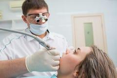 Le dentiste de docteur traite des dents d'une belle patiente de jeune fille La femme à la réception au dentiste de Doctor de dent Photo stock