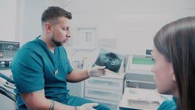 Le dentiste de patient et de dentiste A tenant un rayon X et expliqué lui banque de vidéos