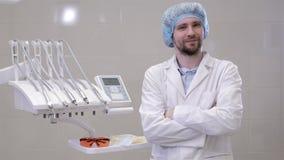 Le dentiste de sourire avec ses bras a croisé dans sa pratique dentaire dans l'hôpital banque de vidéos