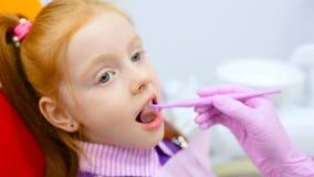 Le dentiste des enfants examine les dents et la bouche d'une petite fille rousse mignonne dans une chaise dentaire jaune-rouge banque de vidéos