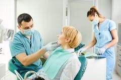 Le dentiste examine les dents de la fille patiente photographie stock