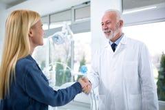 Le dentiste expérimenté et le patient satisfaisant sont manipulés Photo stock