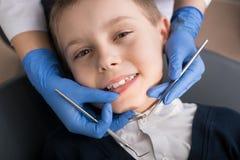 Le dentiste féminin examine les dents de l'enfant patient photographie stock libre de droits