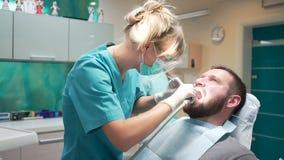 Le dentiste féminin vérifie vers le haut des dents du patient masculin steadicam banque de vidéos