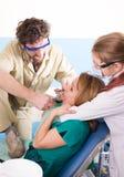 Le dentiste fou traite des dents du patient fâcheux Le patient est terrifié Images stock