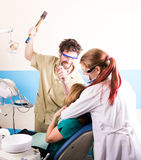 Le dentiste fou traite des dents du patient fâcheux Le patient est terrifié Photographie stock