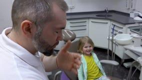 Le dentiste joue avec une fille qui s'assied dans la chaise clips vidéos