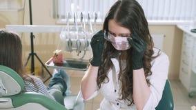 Le dentiste lentement de tir de docteur de steadikam prend des verres transparents protecteurs fonctionnants de chariot à hibou a banque de vidéos