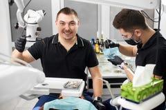 Le dentiste masculin avec les accolades en céramique sourit à l'appareil-photo tandis qu'un autre travaille avec les instruments  photographie stock libre de droits