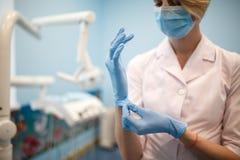 Le dentiste met des gants avant l'opération photo libre de droits
