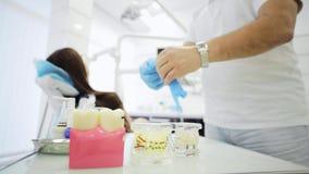 Le dentiste met les gants bleus de latex au-dessus de la table préparant pour travailler dans la clinique banque de vidéos