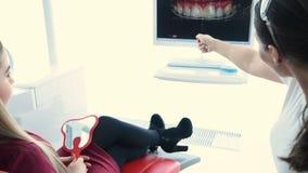 Le dentiste montre au patient un instantané de ses dents banque de vidéos