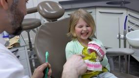 Le dentiste montre un modèle de mâchoire à l'enfant clips vidéos