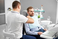 Le dentiste prépare le patient pour l'examen dans la chaise dentaire image stock