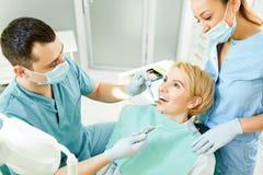 Le dentiste traite les dents de la fille patiente photos stock