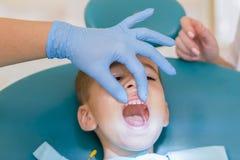Le dentiste traite un boy& x27 ; dents de s Children& x27 ; art dentaire de s, art dentaire pédiatrique Un stomatologist femelle  photos libres de droits