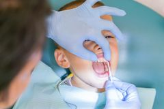 Le dentiste traite un boy& x27 ; dents de s Un petit patient dans la chaise dentaire sourit Dantist traite des dents fin vers le  image stock