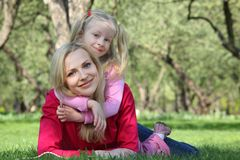 Le descendant embrasse la mère se trouvant sur l'herbe Photos stock