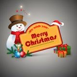 Le deseamos el texto de la Feliz Navidad, bolas de la Navidad y el muñeco de nieve Fotos de archivo