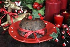 Le dessert anglais de Plum Pudding de Noël de style avec les décorations de fête traditionnelles se ferment  Photographie stock libre de droits