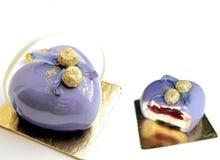 Le dessert de forme de coeur pourpre avec des décorations d'or et l'anneau blanc de chocolat ont découpé en tranches images stock