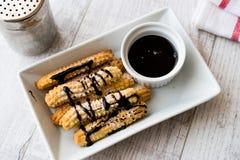 Le dessert espagnol Churros avec la crème au chocolat/a fait la pâte cuire au four douce Photos libres de droits
