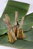 Le dessert thaïlandais enveloppé dans la banane part avec la longue noix de coco Image libre de droits