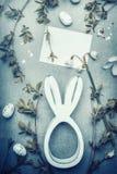 Le dessin de carte de Pâques avec le jouet de lapin, les oeufs, les branches de ressort et le lis de la vallée fleurit Image libre de droits