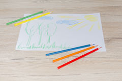 Le dessin de couleur du ` s d'enfant sur un livre blanc avec la couleur crayonne Photo libre de droits