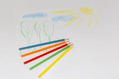 Le dessin de couleur du ` s d'enfant sur un livre blanc avec la couleur crayonne Images stock
