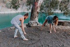 Le dessin heureux de couples forme au sol avec un bâton pour l'amusement en nature Photographie stock