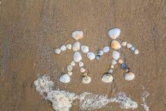 Le dessin sur le sable est couple dans l'amour Photographie stock