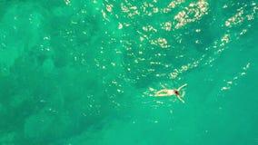 Le dessus aérien a abattu d'une natation de jeune femme en mer Photographie stock libre de droits