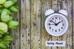 Le dessus de concept de ressort de temps heures d'été en avant regardent vers le bas avec l'horloge blanche et les tulipes vertes images stock