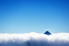 Le dessus de la montagne au-dessus des nuages Images stock
