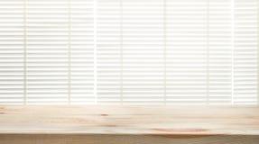 Le dessus de table en bois avec la fenêtre de tache floue shutters le fond de rideau images stock