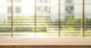 Le dessus de table en bois avec la fenêtre de tache floue shutters le fond de rideau image libre de droits