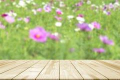 Le dessus de table en bois sur les fleurs colorées dans le jardin a brouillé le backgro Photographie stock libre de droits