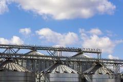 Le dessus des constructions métalliques de l'élévateur à grains sur le fond du ciel image libre de droits