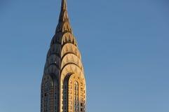 Le dessus du bâtiment de Chrysler s'est allumé par la lumière d'or au lever de soleil Images stock
