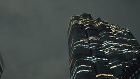 Le dessus du bâtiment de tour dans le centre ville de nuit, a illuminé des gratte-ciel au fond de ciel banque de vidéos