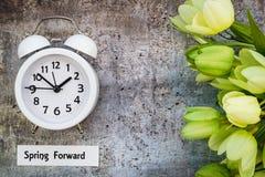 Le dessus en avant de concept de ressort de temps heures d'été regardent vers le bas avec l'horloge blanche et les tulipes vertes Image libre de droits