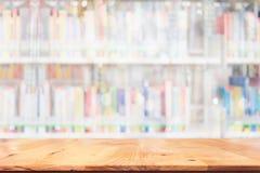 Le dessus vide de la table en bois avec a brouillé beaucoup de livres sur l'étagère dedans Photographie stock