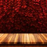 Le dessus vide de la table en bois avec le rouge abstrait laisse le Ba naturel de mur images stock