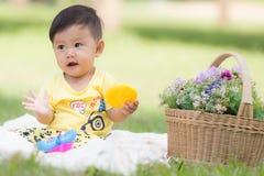 Le det asiatiska pojkelilla barnet sitt på vit bomull i de gröna grasna royaltyfria bilder