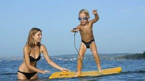 Le det förtjusande barnet som tycker om surfboarding bodyboard för blått hav långsam rörelse stock video
