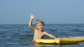 Le det förtjusande barnet som tycker om surfboarding bodyboard för blått hav långsam rörelse arkivfilmer