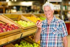 Le det hållande äpplet för hög man royaltyfri foto