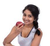 Le det kvinnliga innehavet ett äpple Arkivfoto