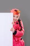 Le det lilla ung flickabarnet i höstvinterkläder klå upp laget och hatten som rymmer ett vitt bräde för tomt affischtavlabaner Arkivfoton